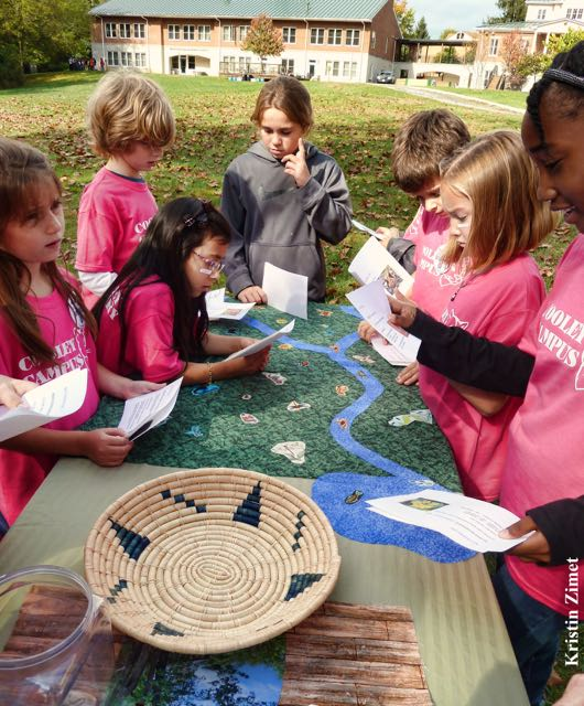 Children cooperating to earn points on The Green Board
